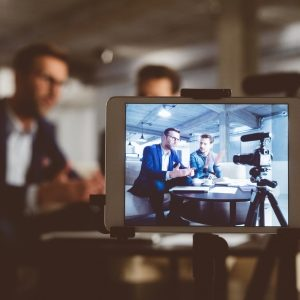Two bloggers on digital tablet screen. Businessman with male guest recording a video blog on camera. Behind the scenes of a business vlog. (Two bloggers on digital tablet screen. Businessman with male guest recording a video blog on camera. Behind the